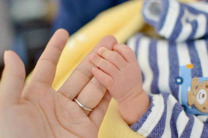 母の手を握る赤ちゃんの手